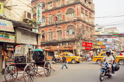 Motorcycle driving on busy street with car traffic and antique rickshaw Royalty Free Stock Photos