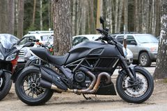 Motorcycle Ducati Diavel matt black. Right side view against the background of cars and trees on a cloudy day Stock Image