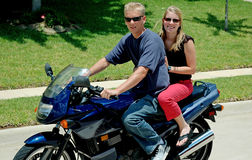 Motorcycle Duo. Two young adults ride on a motorcyle together Royalty Free Stock Photography