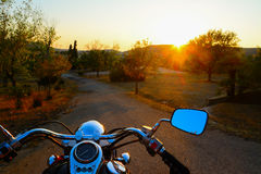 Motorcycle on the edge of the road at sunset Stock Images