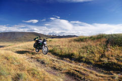 Motorcycle enduro traveler alone under a blue sky with white clouds on a background of mountains with  snow ice covered peaks and Royalty Free Stock Images