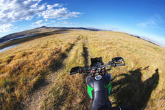 Motorcycle enduro traveler standing on high mountain road fish-eye view. Meadows of yellow grass in Altai Mountains, Siberia, Russia Stock Photo