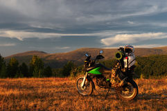 Motorcycle enduro traveler with suitcases standing on a wide orange sunset dawn mountain meadow plateau Stock Photo