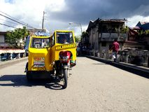 A motorcycle fitted with additional wheels and a cab is turned into what is called a tricycle. SAMAR, PHILIPPINES - NOVEMBER 10, 2015: A motorcycle fitted with Stock Photography