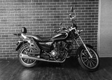 Motorcycle in front of Interior Brick Wall Stock Photo