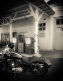 Motorcycle in front of old gas station. Motorcycle is in front of an old gas station. Soft-drawn, black and white picture royalty free stock images