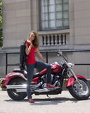Motorcycle and Girl. Young and pretty girl standing next to a motorcyle Royalty Free Stock Images
