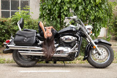 Motorcycle Girl. Girl with leather jacket bending over motorcycle Stock Photography