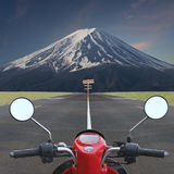 Motorcycle go to volcano and wooden sign in turn left and right. Stock Photography