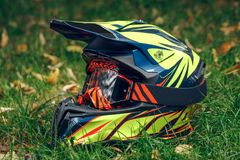 Motorcycle helmet with glasses for protection dry fallen leaves over greem grass. Stock Photos