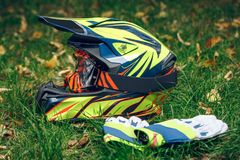 Motorcycle helmet with gloves and goggles on dry fallen leaves stock photos