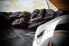 Motorcycle helmet, gloves, and road maps on a wooden table. Journey Dream. Travel route royalty free stock photo