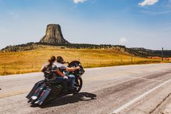 Motorcycle passing Devil`s Tower, Wyoming royalty free stock photography