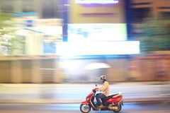 Motorcycle in Ho Chi Minh city. Side view of motorcycle driving down street with motion blur in Ho Chi Minh city, Vietnam Stock Photo