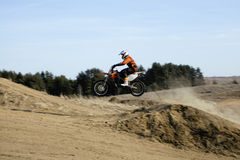 Motorcycle jump from springboard in meadow outside Stock Image