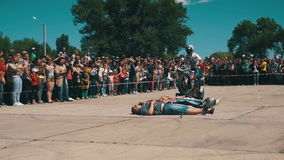 Motorcycle jump on the trampoline through lying people. Moto Trick. Stunt Moto Show. Slow Motion stock footage