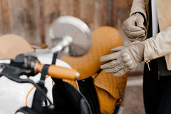 Motorcycle kaferacers. Girl dress leather gloves. Beige leather gloves. Gloves for motorcycle riding. Brown bike seat. Royalty Free Stock Photos