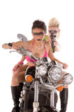 Motorcycle Madness. Two beautiful gun toting young woman in in high fashion makeup and hair in bikinis on a motorcycle Stock Image