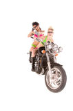 Motorcycle Madness. Two beautiful gun toting young woman in in high fashion makeup and hair in bikinis on a motorcycle Royalty Free Stock Photo