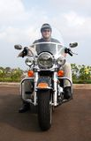 Motorcycle Man. A man smiles at the camera in a head-on pose of him and his black motorcycle Stock Photo
