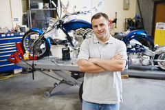 Motorcycle Mechanic. Portrait of a confident male mechanic standing with hands folded at motorcycle workshop stock photography