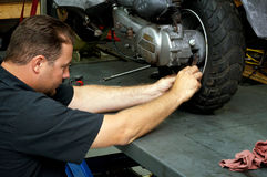 Motorcycle mechanic fixing rear tire Stock Photos