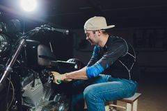 Motorcycle mechanic repairing engine under supervisors guidance. video camera, laptop to view the inside of the engine royalty free stock image