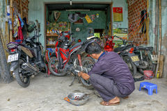 Motorcycle mechanic repairing flat tire scooter Stock Image