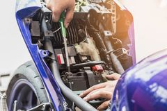 Motorcycle mechanic replaces a battery. maintenance selective. Focus Royalty Free Stock Photo