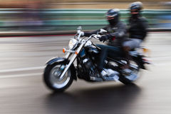 Motorcycle in motion. Driving motorcycle with two men, shown in motion blur, created by panning the camera Royalty Free Stock Photos
