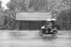 Motorcycle motion riding through gale rain on front wooden house Royalty Free Stock Images