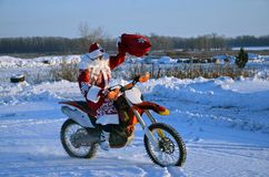 On a motorcycle motocross Santa Claus welcomes Stock Photo