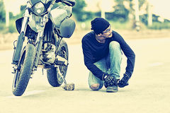 Motorcycle parked in country road with Biker    tying his shoes Royalty Free Stock Photos