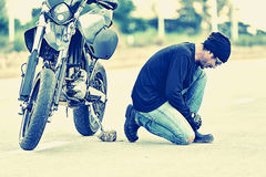 Motorcycle parked in country road with Biker    tying his shoes Royalty Free Stock Photo