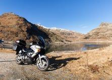 Motorcycle parked next to Lake Montespluga Stock Photo
