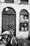 Motorcycle Parked at Rustic Entry. An artistic black and white image of an old motorcycle a royal enfield parked in front of a broken down building in India Royalty Free Stock Photos