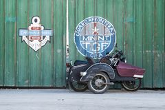 Motorbike with pillon passenger in front of green wooden gate with stock photos