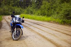 Motorcycle on path. Motorcycle on dirt road after a rain Royalty Free Stock Photography
