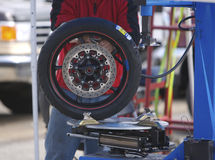 Motorcycle Pit. Man at Motorcycle Race working on a tire royalty free stock images