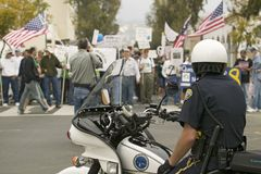 A motorcycle policeman looks at protesters against George W. Bush and the Iraq War at an anti-Iraq War protest march in Santa Barb Stock Photo