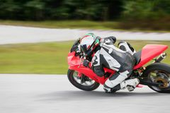 Motorcycle practice leaning into a fast corner on track.  stock photos