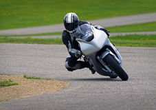 Motorcycle Racer. A sportbike motorcycle racer navigates a curve at the race track stock image