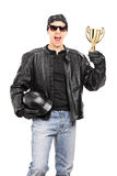 Motorcycle racer holding a gold cup Royalty Free Stock Images