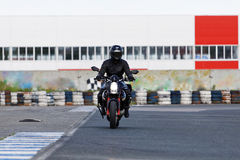 A motorcycle racer takes a practice run on a sports track. A motorcycle racer in black uniform takes a practice run on a sports track royalty free stock photos