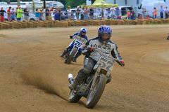 Motorcycle racers in action. Dirt motorcycle racers on the race track royalty free stock photos