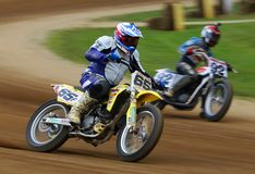 Motorcycle racers fight for the lead. Dirt motorcycle racers on the race track stock photo