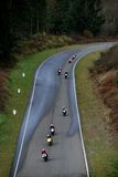 Motorcycle racing. Group of motorcycle riders speeding down a hill Stock Images