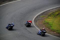 Motorcycle racing. Three motorcycles in a tight race cornering Royalty Free Stock Photos