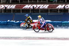 Motorcycle racing in a sharp bend on the ice. Almaty , Kazakhstan - February 15, 2015. Race of two motorcyclists on ice. International competitions in motorcycle stock images