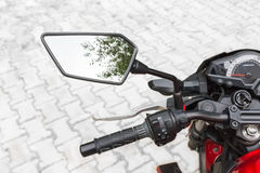 Motorcycle rear view mirror. Motorcycle rear view mirror and reflection of blue sky and tree Stock Photography